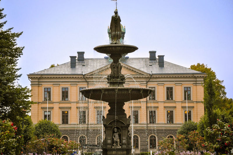 Low angle view of fountain against building in city