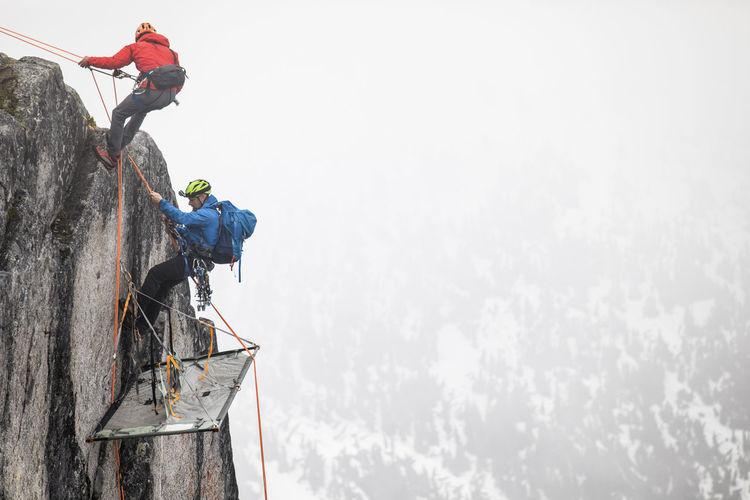 People working on rock against sky