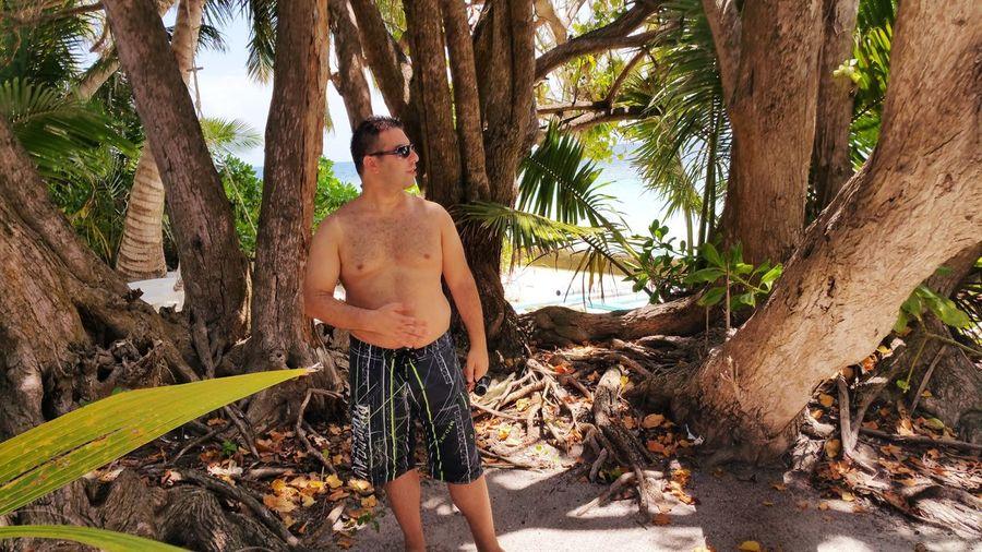 Shirtless Man Standing Against Tree Trunks
