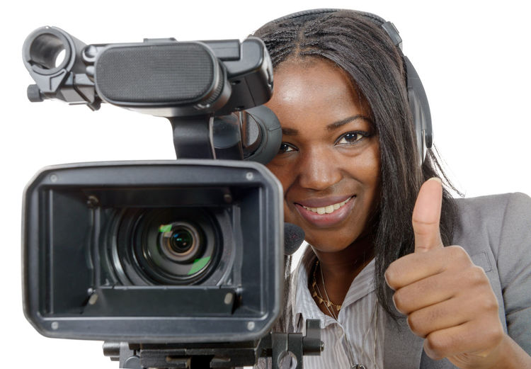 Portrait of young woman photographing against white background