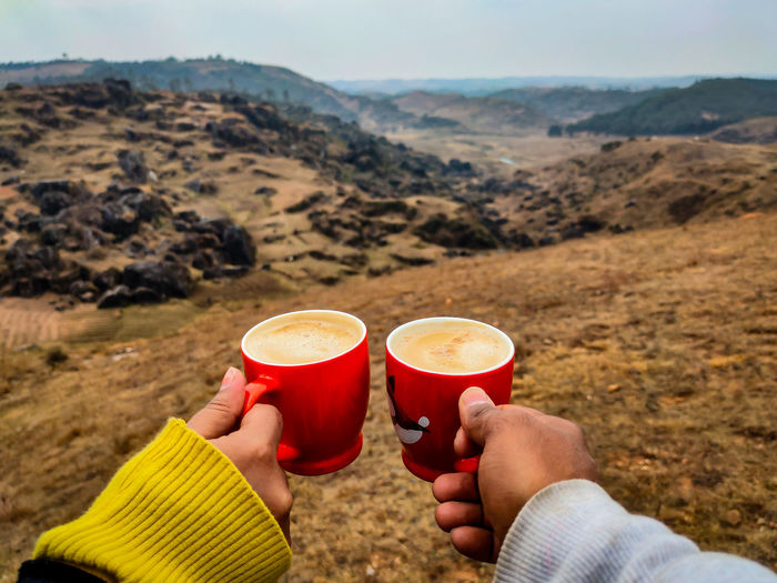 Cropped hand of couple holding coffee cup against landscape