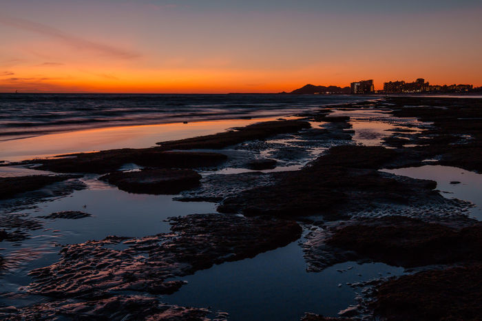 Sunset over a rocky beach at Puerto Penasco (Rocky Point) Mexico. Reflection Sea Beach Water Sunset Nature Sky Silhouette Day Outdoors Tranquility Sunrise Silhouette Scenics Beauty In Nature No People Travel Destinations Tranquil Scene Horizon Over Water