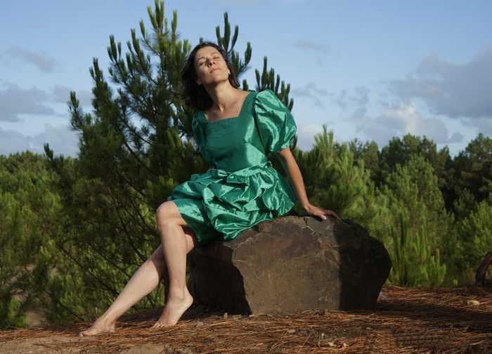 Full Length Of Woman Wearing Green Dress While Sitting On Rock