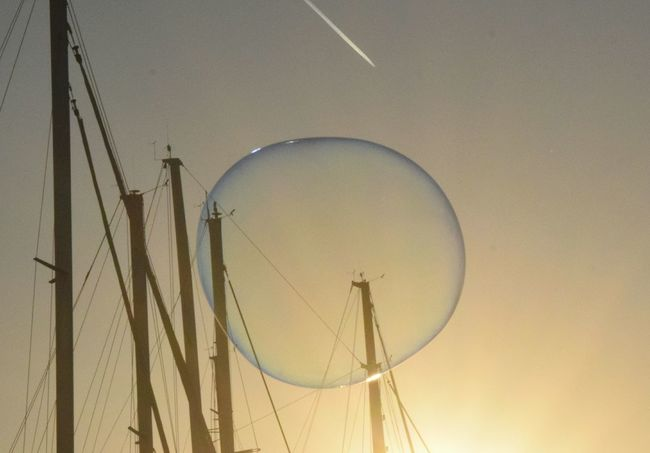 A soap bubble in collision with an airplane Barcelona Mediterranean  Winter Day Outdoors City Travel Destinations Boat Masts Pierce Collision Course Marina Sky Soap Bubbles Floating Plane Round Trans Sunset will the plane hit the bubble??