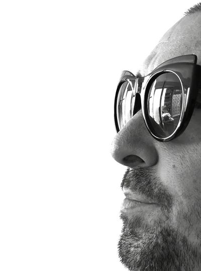 Close-up of young man wearing sunglasses against white background
