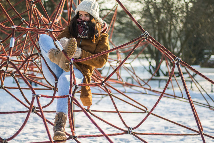Full Length Of Woman Resting On Ropes At Snow Covered Park