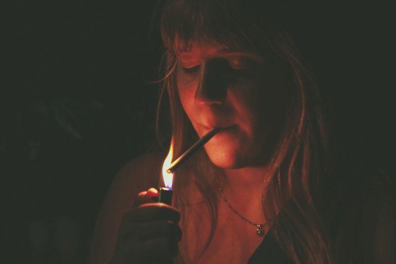 Close-up of woman lightning cigarette in darkroom