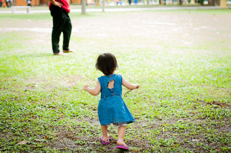 Full length rear view of woman walking on field