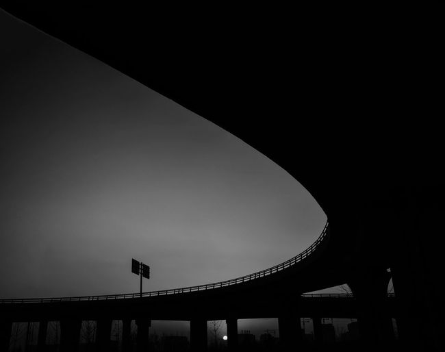 Low angle view of silhouette bridge against clear sky