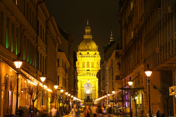 Budapest, Hungary Architecture Building Building Exterior Built Structure City Clock Group Of People History Illuminated Incidental People Light Lighting Equipment Low Angle View Night Outdoors Place Of Worship Religion Street Street Light The Past Tourism Travel Travel Destinations
