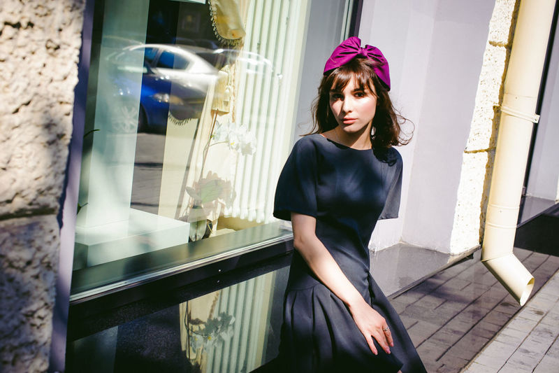 Beautiful young woman in black dress sitting on window