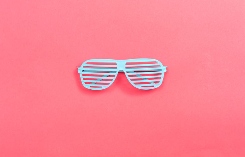 Directly above shot of sunglasses against pink background