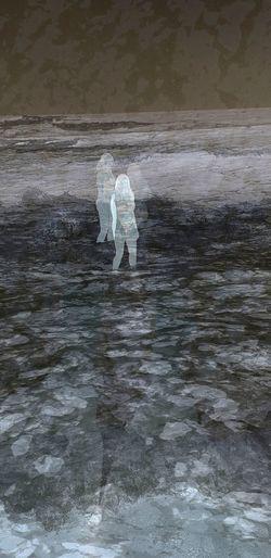 People walking on wet shore