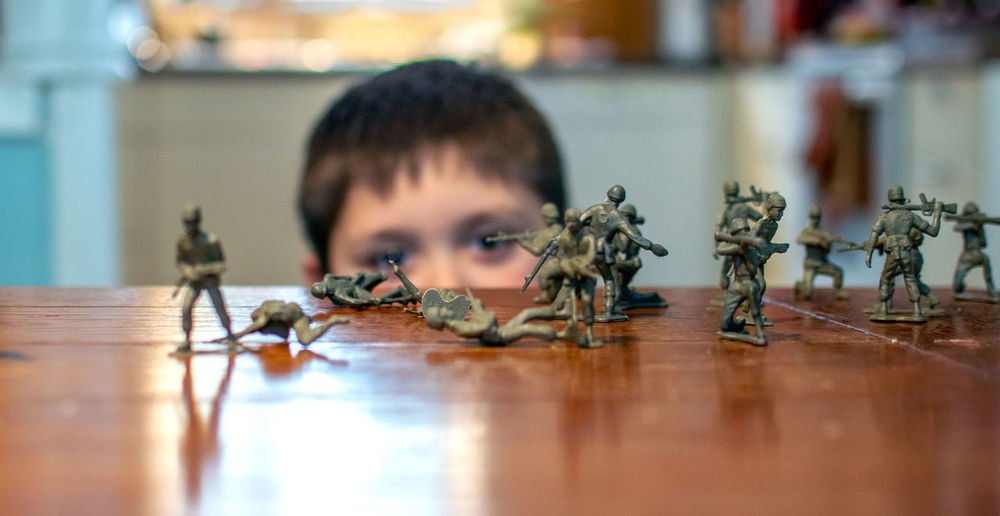 Portrait of boy with toy soldiers  on  a table