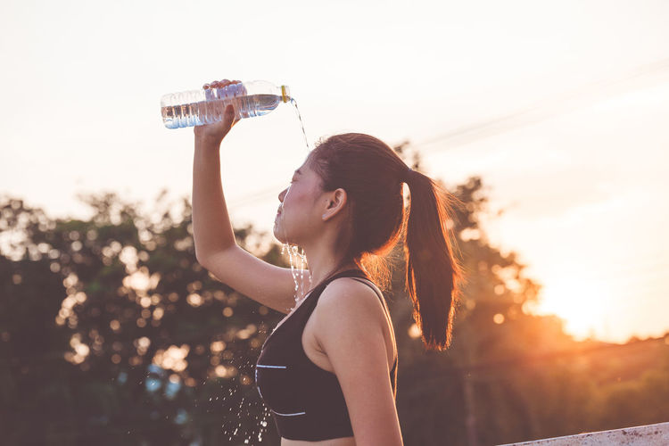 Young woman putting water on face during sunrise