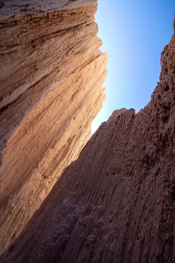 Sunlight and blue sky above a slot canyon