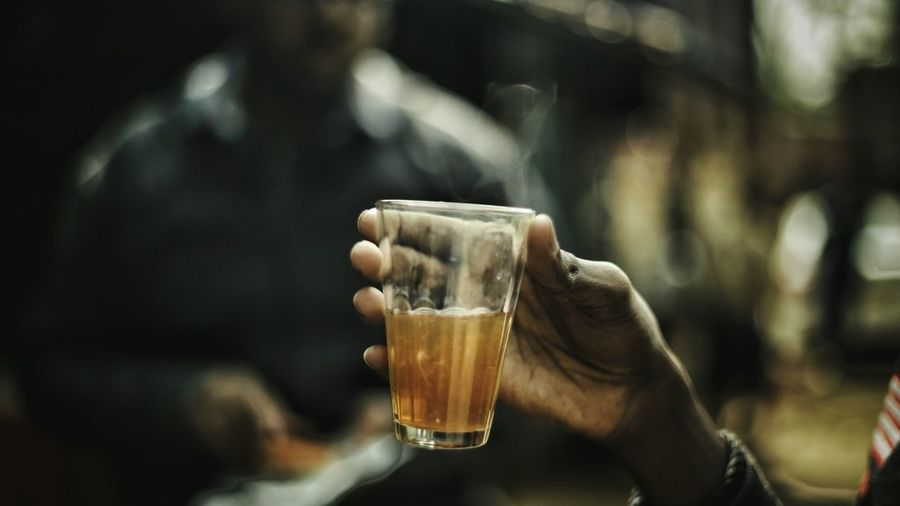 Cropped Hand Of Man Holding Tea Glass