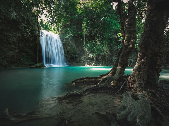 Epic waterfall smooth stream with emerald pond in rainforest. erawan falls, kanchanaburi, thailand.