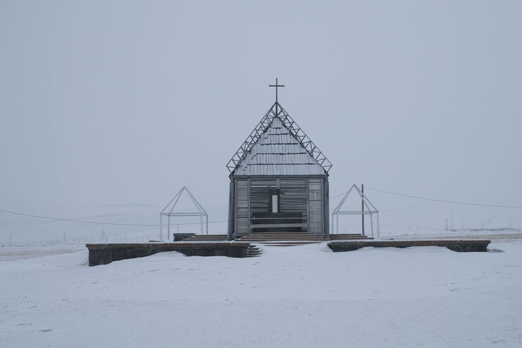 Built structure on snow covered land against clear sky