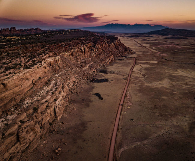 On the edge of a crumbling world Cliffs Dark Desert Drone  Road Scenic Utah Beauty In Nature Car Cliff Cliffside Day Drone Photography Dronephotography Landscape Moody Nature No People Outdoors Scenics Sky Sunset Tranquil Scene Tranquility