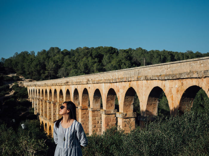 Woman standing against arch bridge