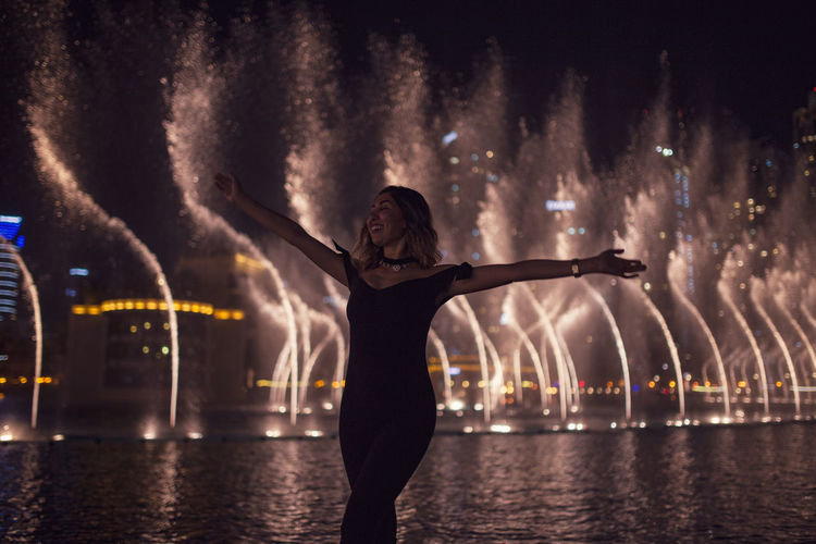 Woman with arms outstretched against fountain in city at night
