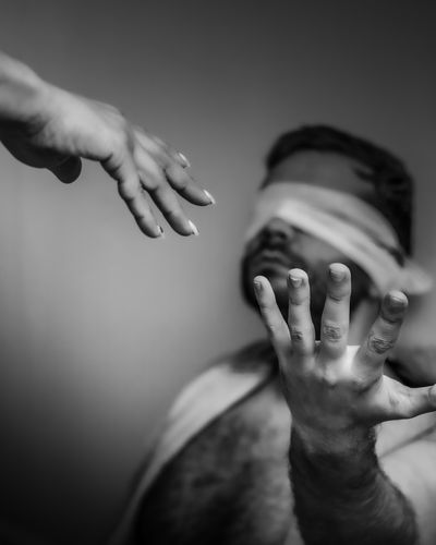 Cropped image of hand reaching towards man with blindfold