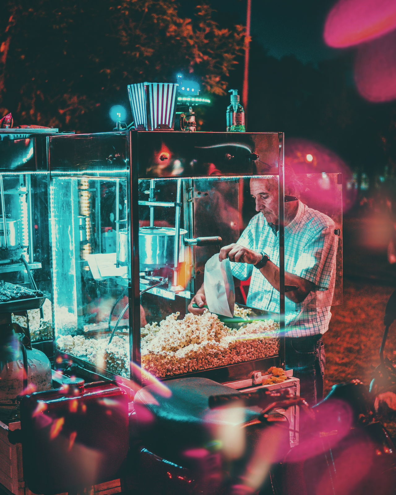 Senior man selling popcorns at night