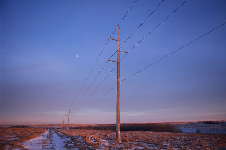 Low angle view of electricity poles on field against sky at dusk