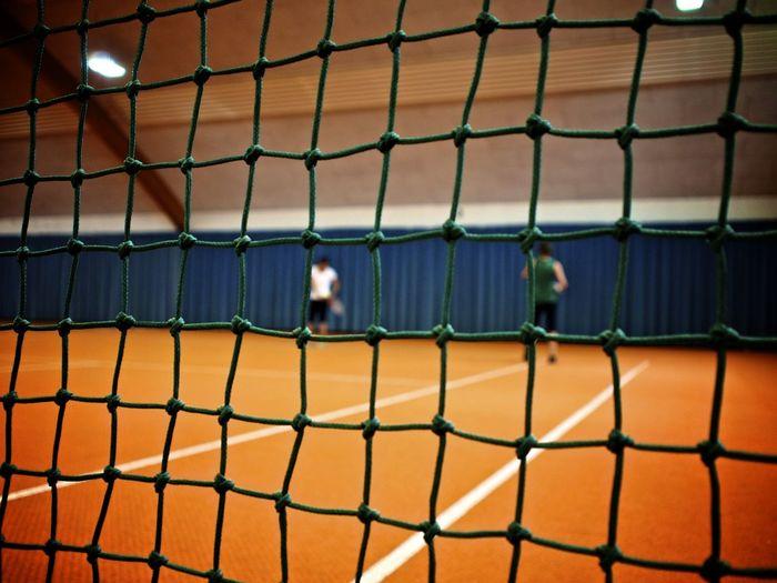 Men Playing At Tennis Court Seen Through Net