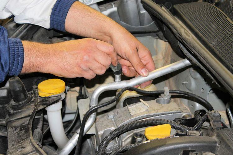 Cropped Hands Repairing Car Engine