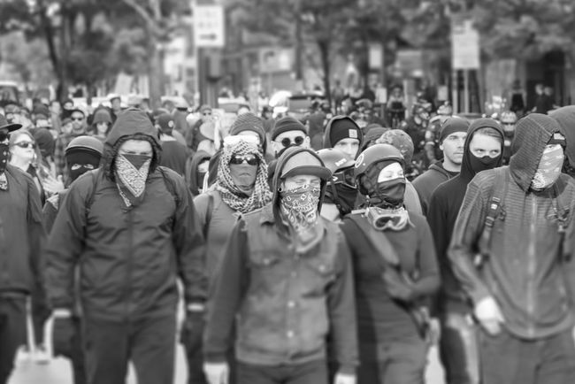 May day protest marchers with masks hiding their faces in Seattle on May 1st 2018. Gang Adult Antifa Architecture City Clothing Criminals Crowd Day Felons Focus On Foreground Group Of People Incidental People Large Group Of People Leisure Activity Lifestyles Men Outdoors Real People Riot Street Thugs Uniform Walking Women The Photojournalist - 2018 EyeEm Awards
