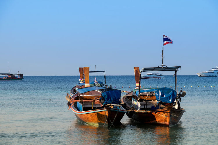 Boats moored at river against clear sky