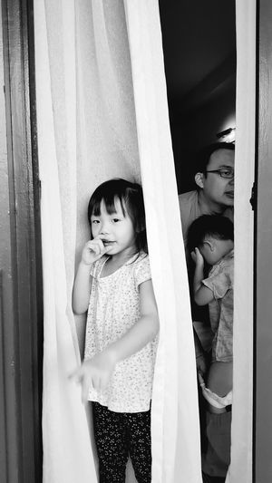 Childhood Lifestyles Elementary Age Girls Hiding Leisure Activity Childhood Standing Indoors  Lifestyles Elementary Age Leisure Activity Three Quarter Length Person Casual Clothing Cute Girls Innocence Looking Down Curtain Looking At Camera In Front Of Hiding
