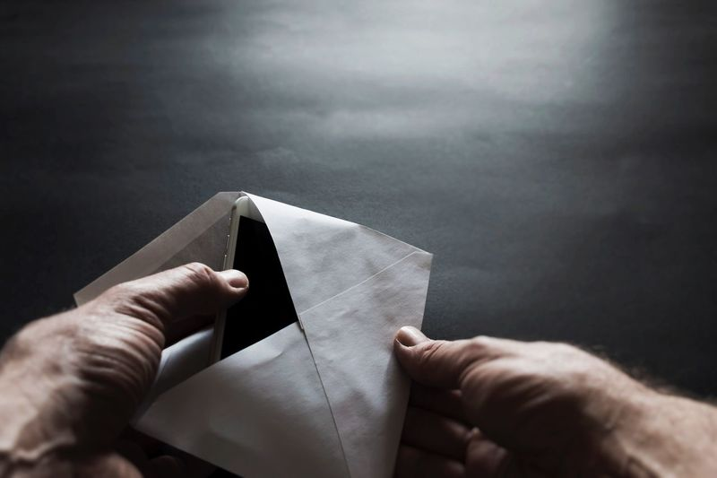 Cropped hands of man holding mobile phone in envelop