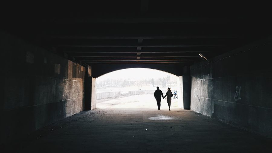 Rear view of silhouette couple walking in tunnel