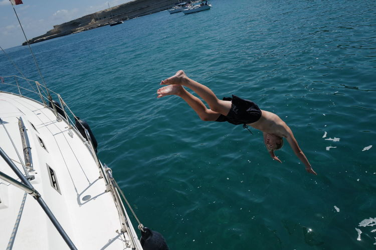 Shirtless man diving from boat into sea