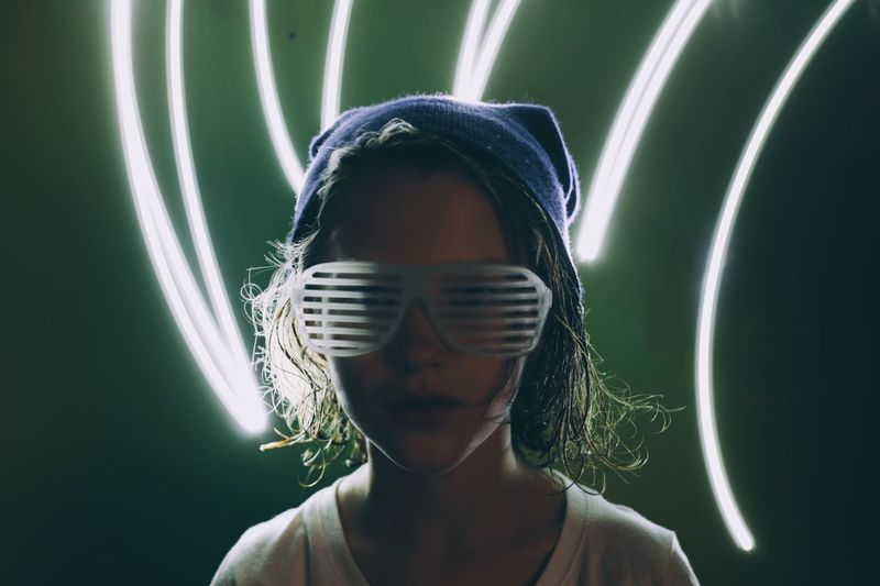 Portrait Of Girl Wearing Novelty Glasses With Light Painting Against Green Background