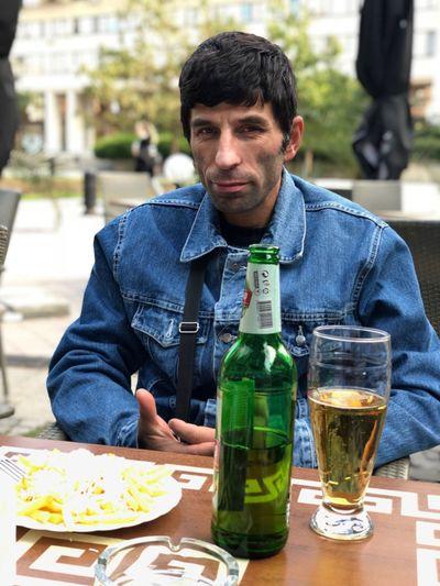 Portrait of man sitting at sidewalk cafe