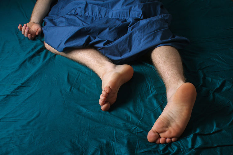 Low section of man lying on bed