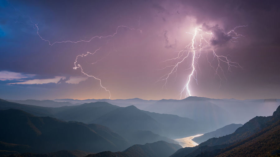 Low angle view of lightning over mountains against sky