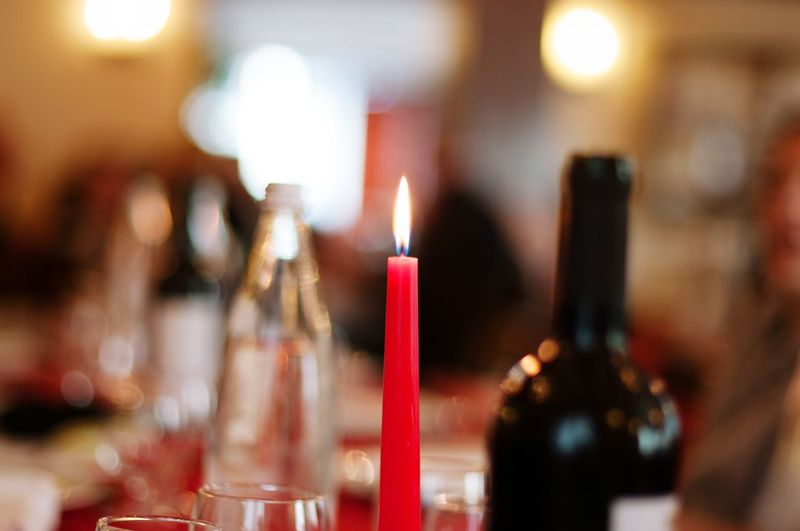 Close-up of burning candle on dining table at home