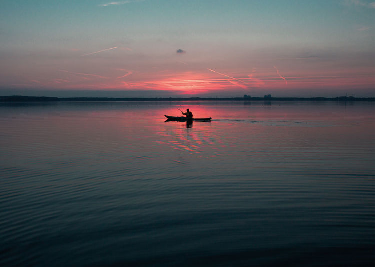 Scenic view of person canoeing at dusk