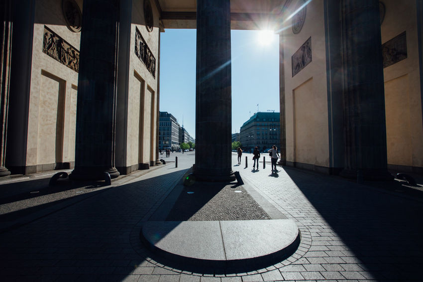 Columns of Brandenburger Tor in Berlin city center against the early morning sun. Against The Sun Anonymous Architecture Berlin Brandenburger Tor Building Built Structure City City Life Closeup Column Day Detail Empty Historic Landmark Morning Outdoors Shadows Silhouette Sunlight The Way Forward Tourists Traffic