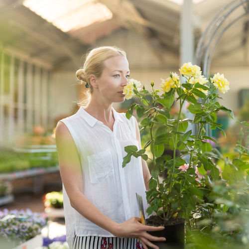 Young woman standing by flowering plants
