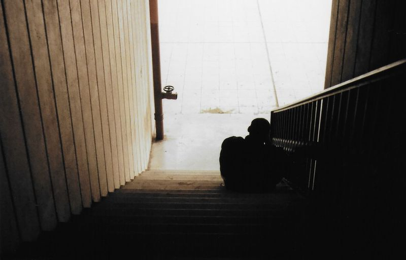 Rear view of silhouette man sitting on staircase in building