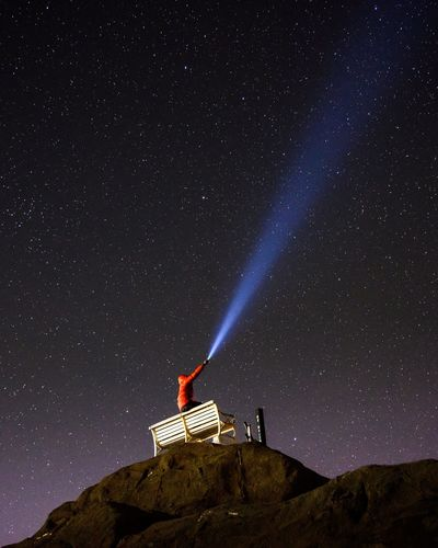 Low angle view of man with flashlight against sky at night