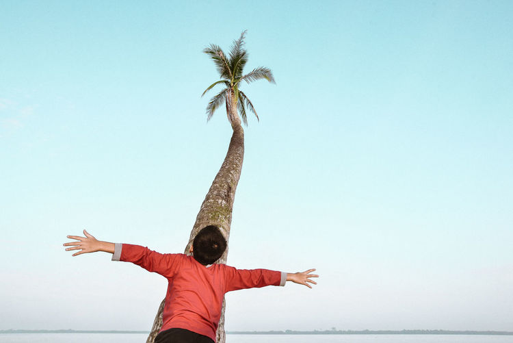 Low section of boy standing with arms outstretched against clear sky