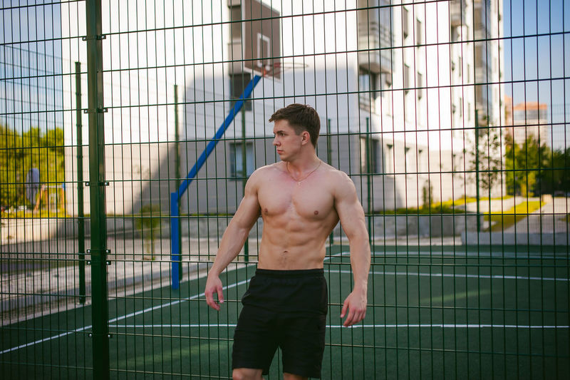 Muscular man standing against fence at park