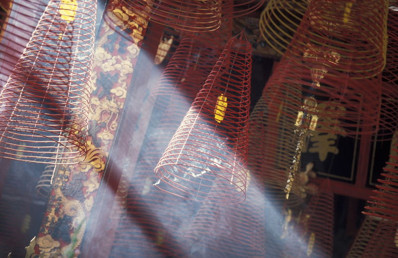 Low angle view of sunlight streaming by spiral incense sticks in temple